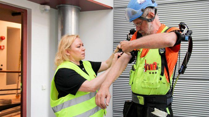 Minna Laine avusti laitteen Markku Koppasen päälle. Skelex puetaan ja kiristetään selkään tukevan rinkan tapaan, minkä jälkeen käsivarsituet kiinnitetään paikoilleen leveillä tarranauhoilla.