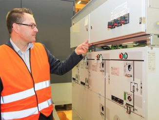 ABB:n Mika Kuusisto esittelee sähkövaraston Suomessa valmistettua ohjaus- ja kommunikaatioyksikköä.